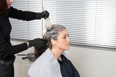 Woman having her hair dyed by beautician at parlor photo