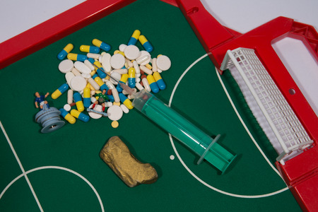 doped: Figures of football players on euro banknotes, syringe and pills