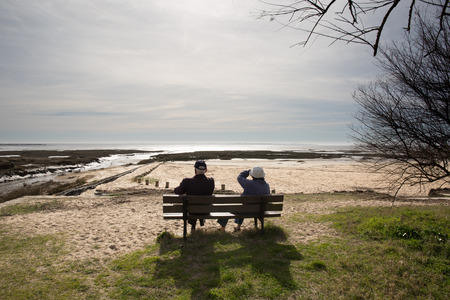 a meeting with a view to marriage: Rear view of a happy romantic senior couple sitting on a park bench Stock Photo
