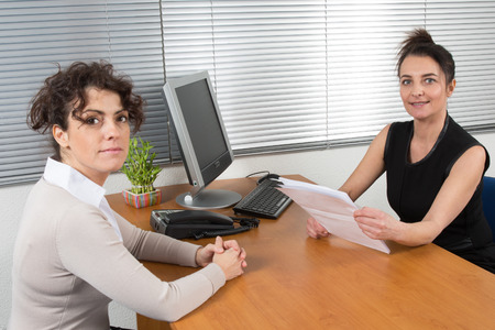 A Business woman receives candidate for  a job at her office photo