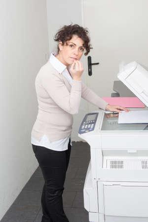 copy machine: Businesswoman having trouble with copy machine