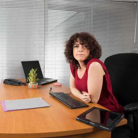 at her desk: Business woman at her desk at office