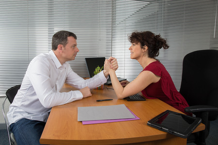 a man and woman with hands clasped arm wrestling photo