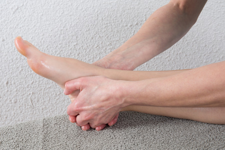 woman receiving a massage on  her painful ankle photo