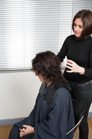 stylist: Stylist cutting split ends on her client at the salon