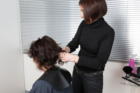 the ends: Stylist cutting split ends on her client at the salon