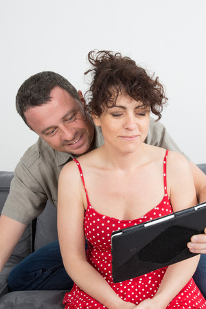 40 to 45 years old: Delighted couple using a tablet computer in their living room