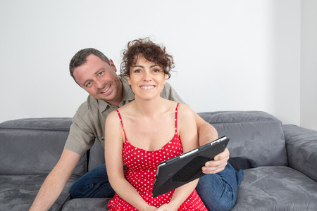 40 45 years: Delighted couple using a tablet computer in their living room