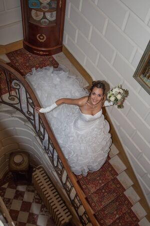 descends: A bride descends a staircase to see her groom Stock Photo