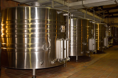 vats: Stainless steel wine vats in a row inside the winery.