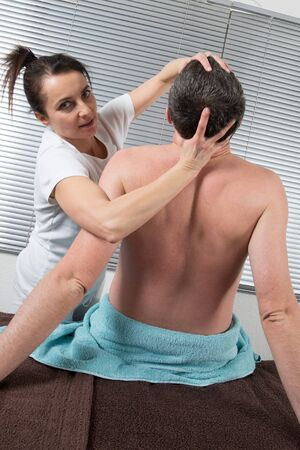 shiatsu: A man Receiving Shiatsu Treatment From a woman therapist Stock Photo