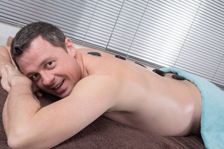 stone therapy: Adult male receiving hot stone therapy at spa center Stock Photo