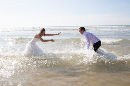 jump suit: Happy just married young couple celebrating and have fun Stock Photo