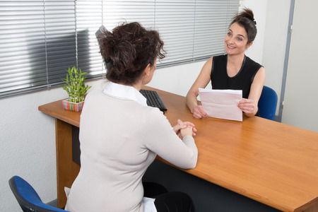 receives: A Business woman receives candidate for  a job at her office Stock Photo