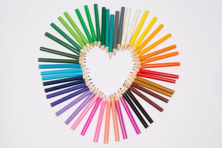 Colored pencils frame heart shaped photo