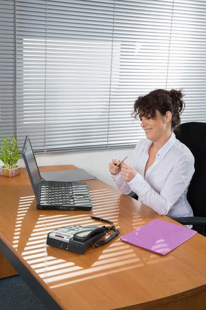 beautiful mature woman: Woman at work using nail file