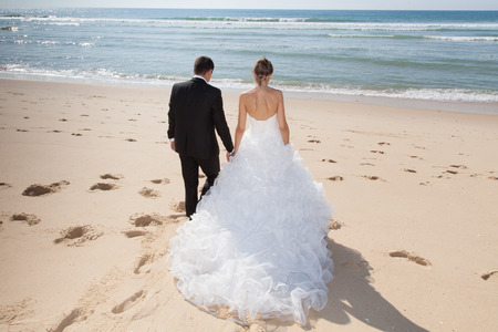 Mooi paar op het strand in bruidsjurk Stockfoto