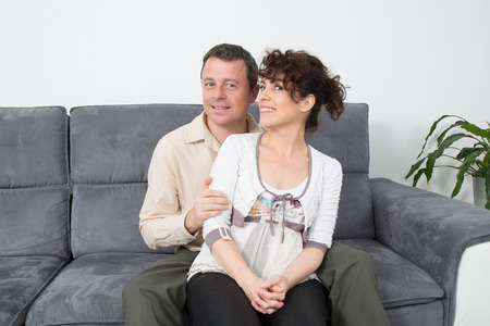 Happy couple relaxing in sofa at home