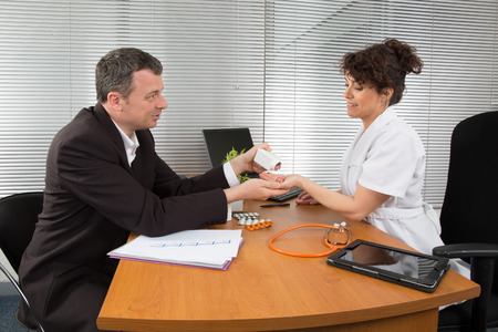 healthcare visitor: Businessman with Female Doctor at her office