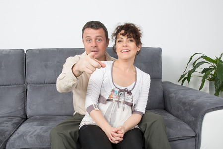 cocooning: Happy couple relaxing in sofa at home