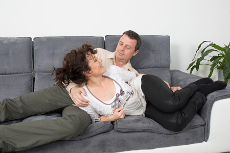 couple on couch: Cheerful couple on their couch