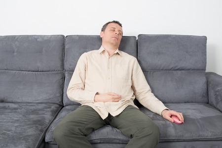 Goodlooking man in causal wear sleeping on sofa. photo
