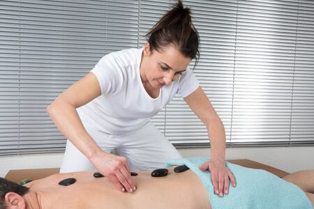 stone therapy: A Man getting stone therapy massage in spa center