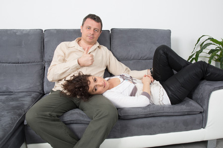 couple on couch: Cheerful couple on their couch smiling at camera at home