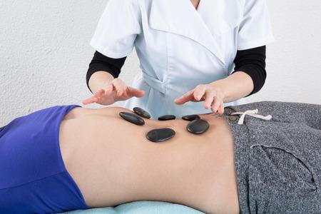 hot stone: Adult woman having hot stone massage Stock Photo