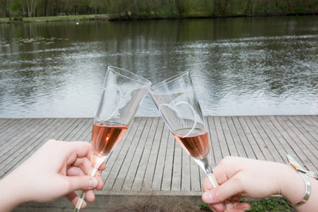 honey moon: Two persons holding a champagne glasses Stock Photo
