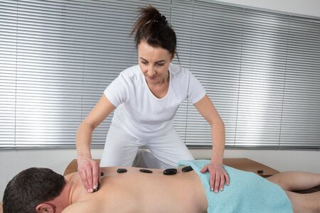hot stone: Adult male receiving hot stone therapy at spa center Stock Photo