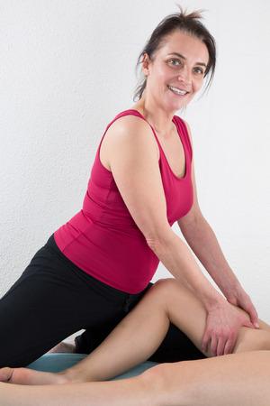 Beautiful young woman getting legs massage