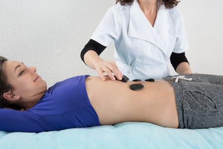 stone massage: Adult woman having hot stone massage in spa salon