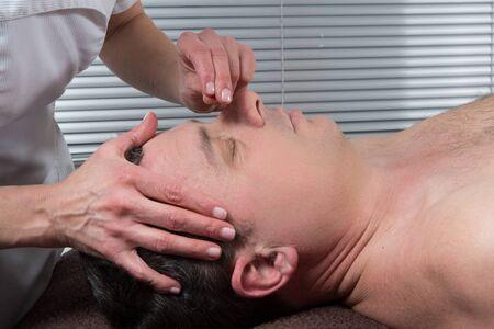 meridians: Man Undergoing Acupuncture Treatment Stock Photo