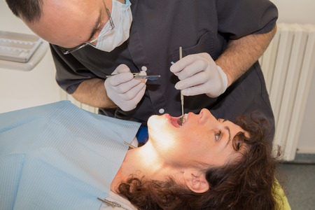 Dentist examining Patient teeth with a Mouth Mirror. photo