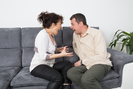 argumentation: Couple screaming at each other on sofa