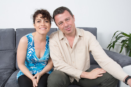Couple being playful on a grey sofa at home. photo