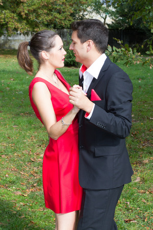 Nice couple in bright clothes dancing on the park photo