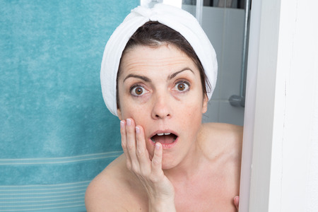 female in douche: Portrait of shocked woman covering her body with towel