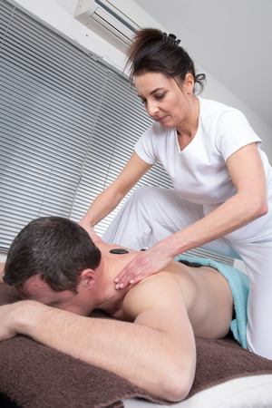 rejuvenate: Adult male receiving hot stone therapy at spa center Stock Photo