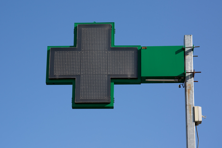cross street with care: Pharmacy sign under blue sky. Green pharmacy cross on a building.