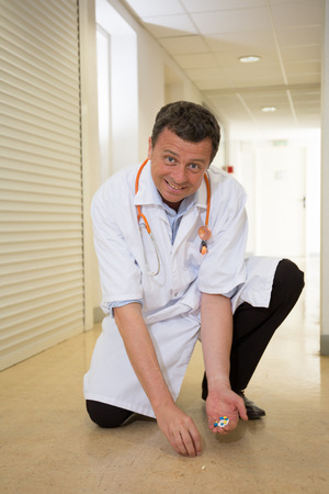 'pick up': Handsome Doctor kneeling to pick up pills on the floor Stock Photo