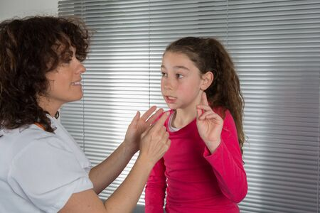 Woman doctor examines a young girls throat photo