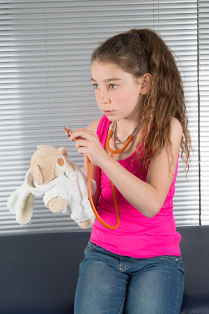 hospital stress: Beautiful girl listens by means of stethoscope as heart of toy bear