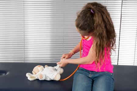 reassurance: La muchacha hermosa escucha por medio de estetoscopio como centro de juguete oso