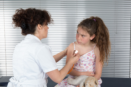 angry teddy: Female doctor examines a young girl not happy