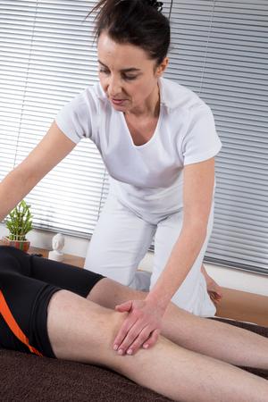 female therapist: Portrait of female therapist doing leg massage Stock Photo