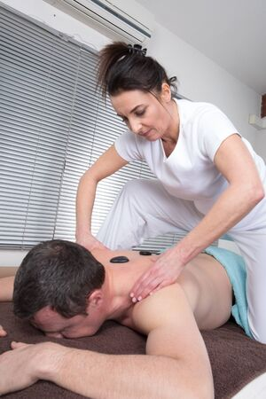 adult male: Adult male receiving hot stone therapy at spa center Archivio Fotografico