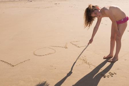 sand writing: Young girl writing on the sand love on holidays