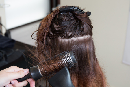 clippers comb: Cropped image of a hairstylist drying the hair of the customer at the beauty salon Stock Photo